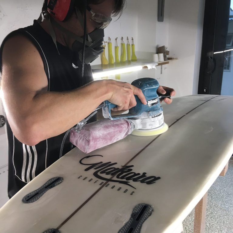Chris sanding a surfboard with a random orbital sander.