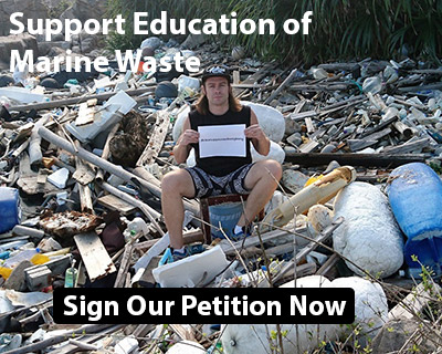 Chris holding a sign sitting on a pile of marine waste.
